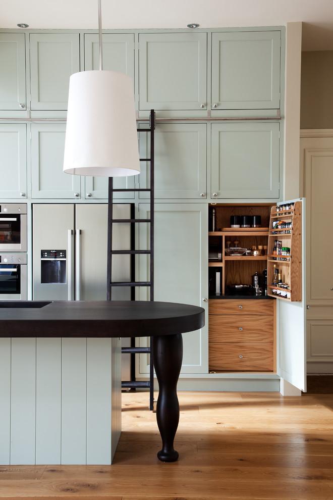 Zweizeilige Klassische Küche mit integriertem Waschbecken, Schrankfronten im Shaker-Stil, Küchengeräten aus Edelstahl, braunem Holzboden, Kücheninsel und blauen Schränken in London