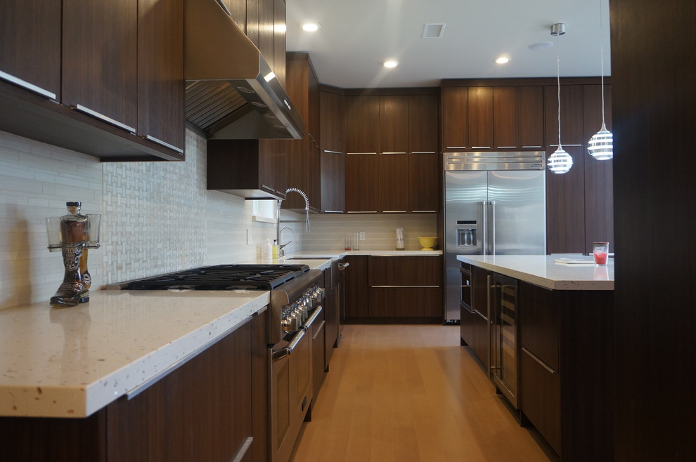 Large minimalist u-shaped light wood floor eat-in kitchen photo in Los Angeles with a farmhouse sink, flat-panel cabinets, dark wood cabinets, quartzite countertops, beige backsplash, mosaic tile backsplash, stainless steel appliances and an island