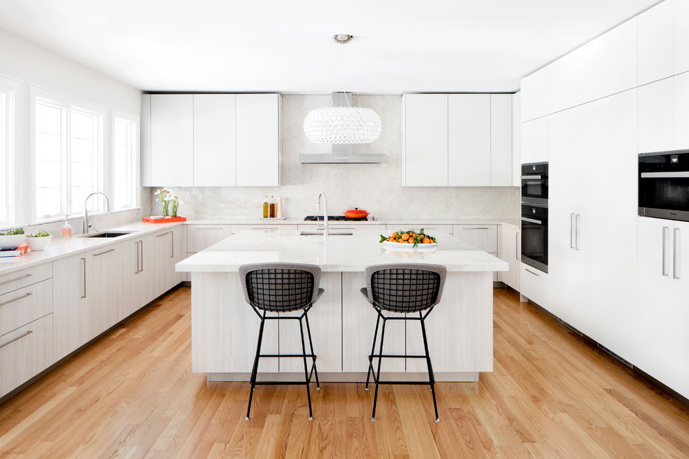 Example of a large trendy u-shaped light wood floor kitchen design in DC Metro with an undermount sink, flat-panel cabinets, quartzite countertops, stone slab backsplash, black appliances, an island, white cabinets and white backsplash