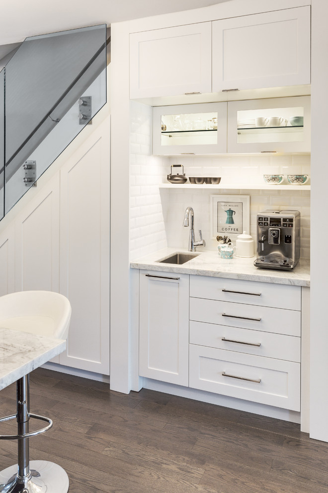 Example of a small trendy single-wall dark wood floor open concept kitchen design in Other with an undermount sink, shaker cabinets, white cabinets, white backsplash, subway tile backsplash, marble countertops, stainless steel appliances and an island