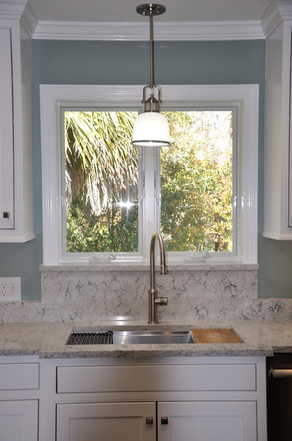 Trendy kitchen photo with an undermount sink, shaker cabinets, white cabinets, quartz countertops and an island
