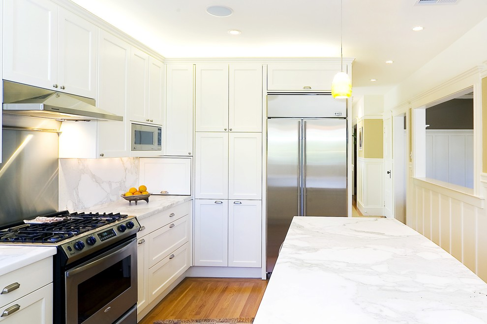 Example of a classic kitchen design in San Francisco with stainless steel appliances, marble countertops and marble backsplash