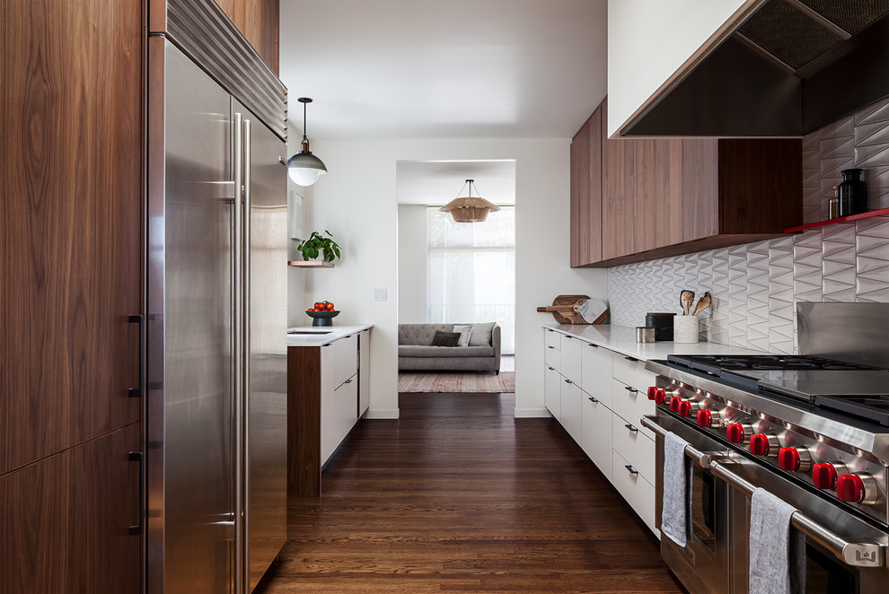 Kitchen - contemporary galley dark wood floor and brown floor kitchen idea in San Francisco with an undermount sink, flat-panel cabinets, white cabinets, gray backsplash, stainless steel appliances and white countertops