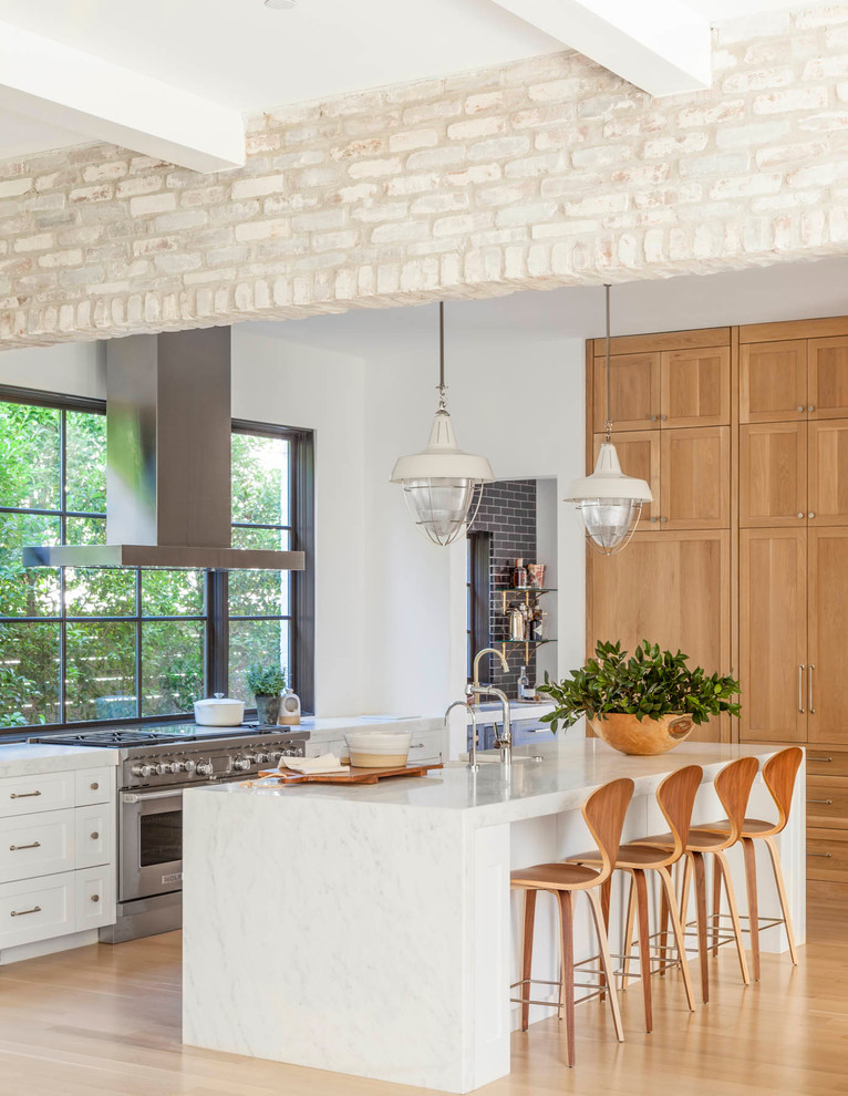 Open concept kitchen - large transitional galley light wood floor and brown floor open concept kitchen idea in Dallas with shaker cabinets, light wood cabinets, stainless steel appliances, an island, a farmhouse sink, marble countertops, window backsplash and gray countertops