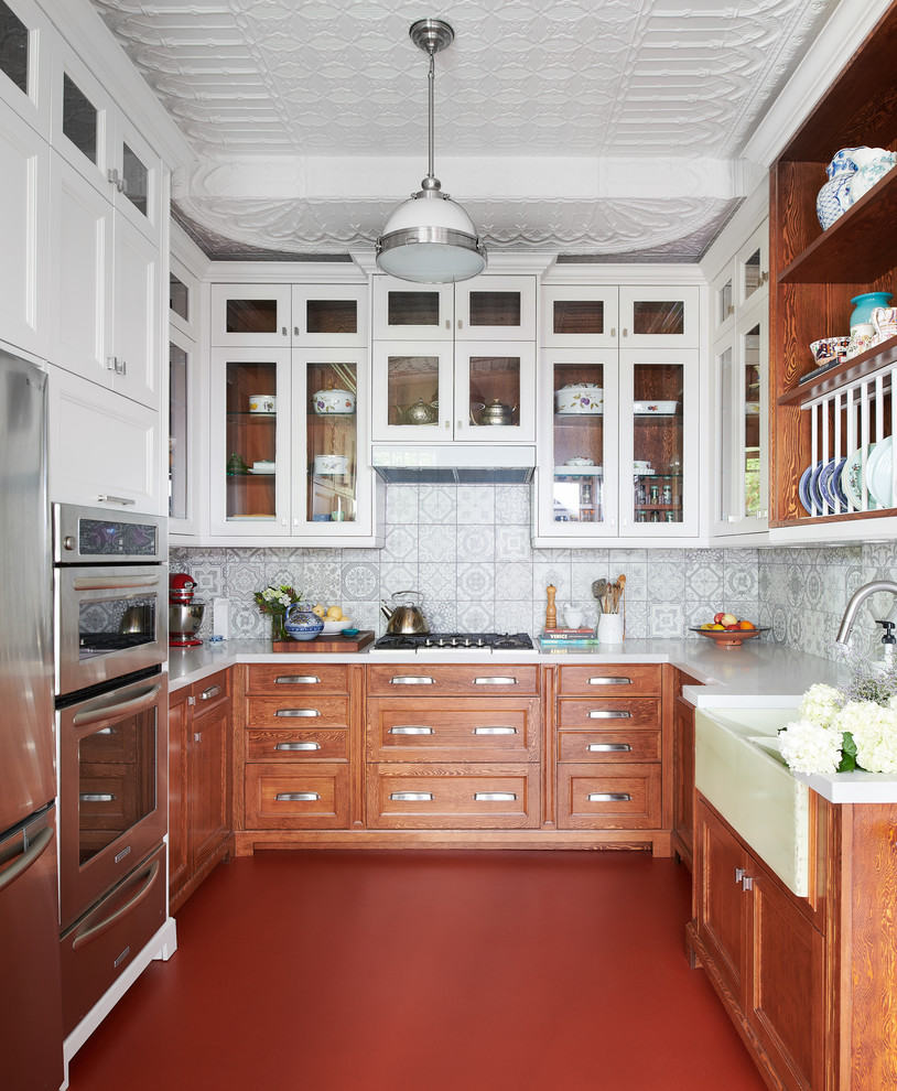Mid-sized eclectic u-shaped red floor and concrete floor enclosed kitchen photo in Toronto with a farmhouse sink, shaker cabinets, medium tone wood cabinets, gray backsplash, ceramic backsplash, stainless steel appliances, no island, white countertops and solid surface countertops