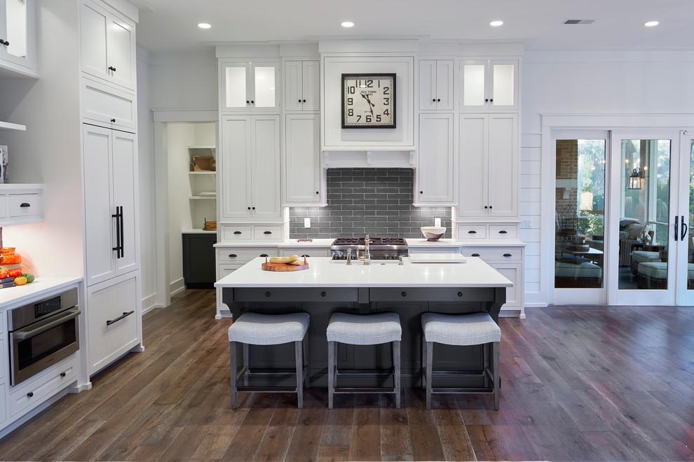 Kitchen - transitional dark wood floor kitchen idea in Atlanta with shaker cabinets, white cabinets, gray backsplash, subway tile backsplash, paneled appliances and an island