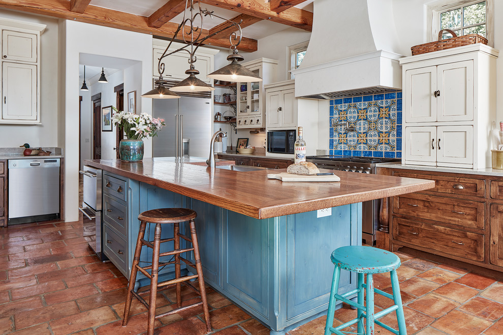Large tuscan u-shaped terra-cotta floor enclosed kitchen photo in Atlanta with shaker cabinets, blue cabinets, wood countertops, multicolored backsplash, stainless steel appliances, an island, a farmhouse sink and brown countertops