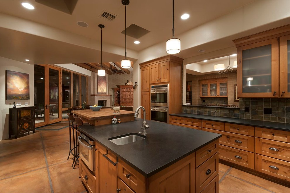 Example of a large classic terra-cotta floor eat-in kitchen design in Phoenix with stainless steel appliances, an undermount sink, shaker cabinets, medium tone wood cabinets, stone tile backsplash, multicolored backsplash and an island