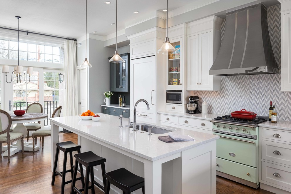 Open concept kitchen - large transitional l-shaped dark wood floor and brown floor open concept kitchen idea in Portland with an undermount sink, recessed-panel cabinets, white cabinets, gray backsplash, stone tile backsplash, paneled appliances, an island, quartz countertops and white countertops