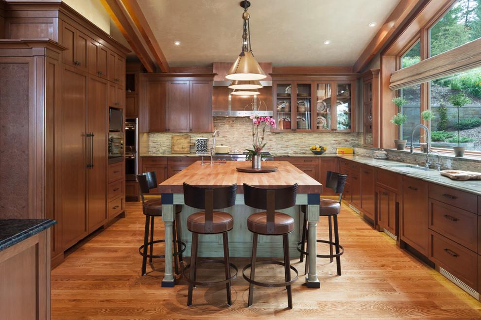 Kitchen - transitional l-shaped medium tone wood floor kitchen idea in Philadelphia with an undermount sink, recessed-panel cabinets, dark wood cabinets, multicolored backsplash, mosaic tile backsplash, paneled appliances and an island