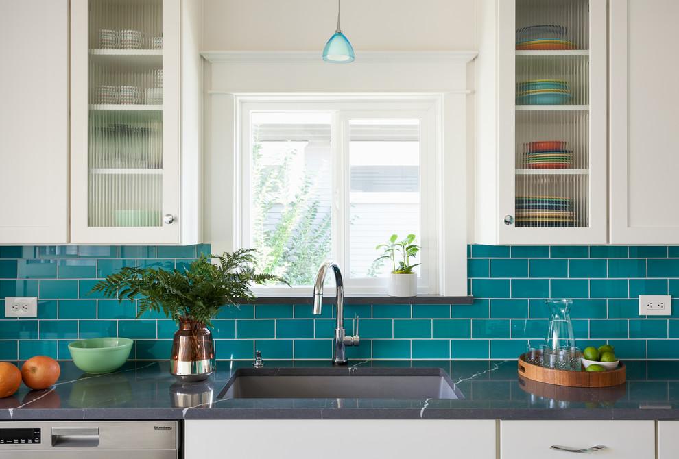 Inspiration pour une cuisine parallèle craftsman fermée et de taille moyenne avec un évier encastré, un placard à porte shaker, des portes de placard blanches, un plan de travail en quartz modifié, une crédence multicolore, une crédence en carreau de verre, un électroménager en acier inoxydable, un sol en vinyl, un sol gris et un plan de travail gris.