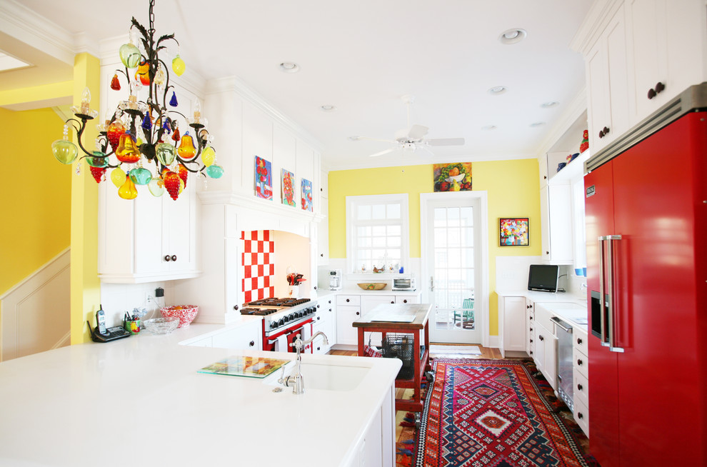 Photo of an eclectic kitchen in Other with coloured appliances, shaker cabinets and white cabinets.