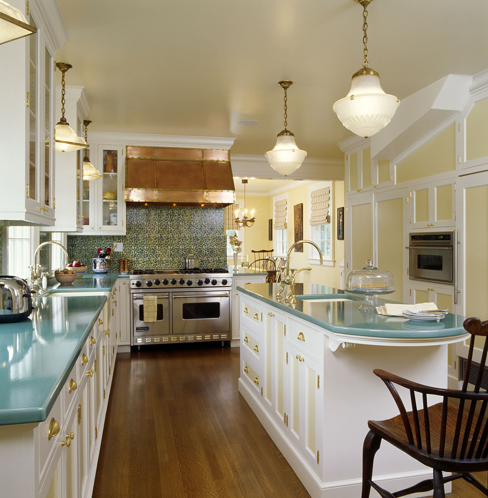 Inspiration for a mid-sized timeless l-shaped medium tone wood floor enclosed kitchen remodel in Santa Barbara with a farmhouse sink, recessed-panel cabinets, white cabinets, green backsplash, paneled appliances, an island, ceramic backsplash and turquoise countertops