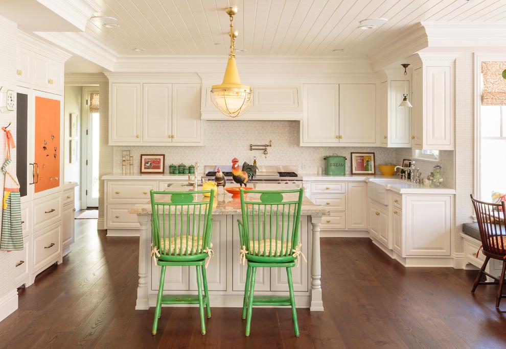 Elegant u-shaped medium tone wood floor eat-in kitchen photo in Los Angeles with a farmhouse sink, raised-panel cabinets, white cabinets, white backsplash, ceramic backsplash, paneled appliances and an island