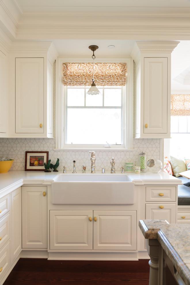 Elegant medium tone wood floor kitchen photo in Los Angeles with a farmhouse sink, recessed-panel cabinets, white cabinets, white backsplash, ceramic backsplash and an island