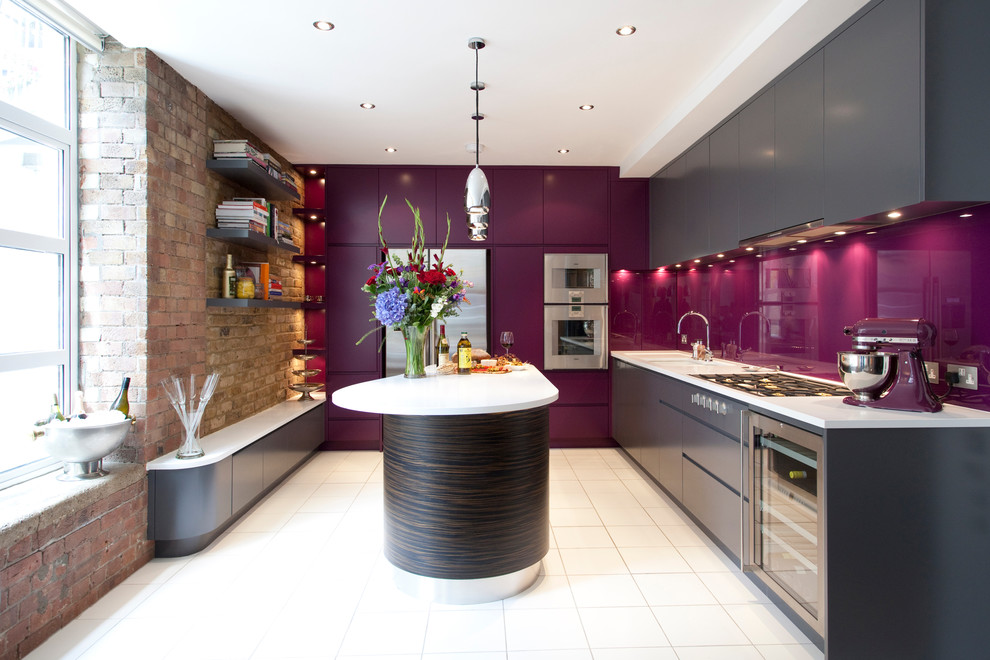 Example of a trendy galley kitchen design in London with an undermount sink, flat-panel cabinets, gray cabinets, glass sheet backsplash, stainless steel appliances and an island