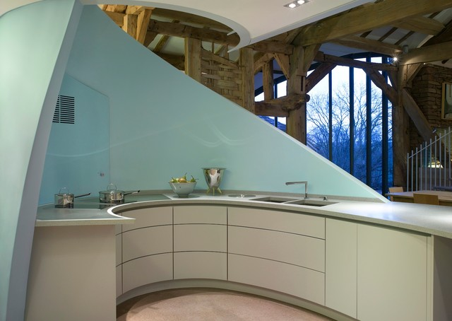 Photo of a large contemporary open plan kitchen in London with a submerged sink, flat-panel cabinets, blue cabinets, composite countertops, white appliances and a breakfast bar.