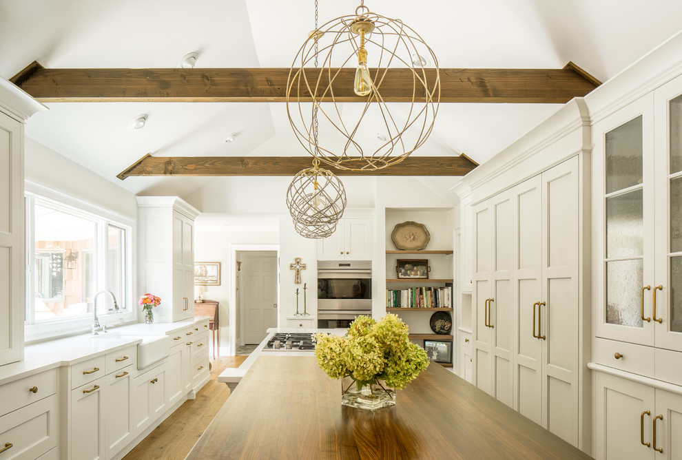 Kitchen - large country u-shaped medium tone wood floor kitchen idea in New York with shaker cabinets, white cabinets, a farmhouse sink, quartz countertops, stainless steel appliances and an island