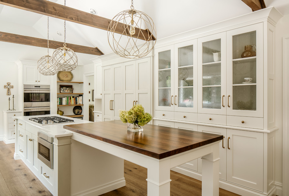 Inspiration for a large cottage u-shaped medium tone wood floor kitchen remodel in New York with shaker cabinets, white cabinets, quartz countertops, stainless steel appliances, a farmhouse sink and an island