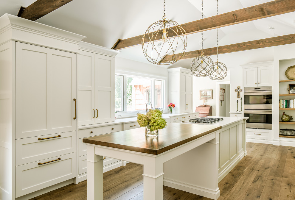 Example of a large farmhouse u-shaped medium tone wood floor kitchen design in New York with shaker cabinets, white cabinets, a farmhouse sink, quartz countertops, stainless steel appliances and an island