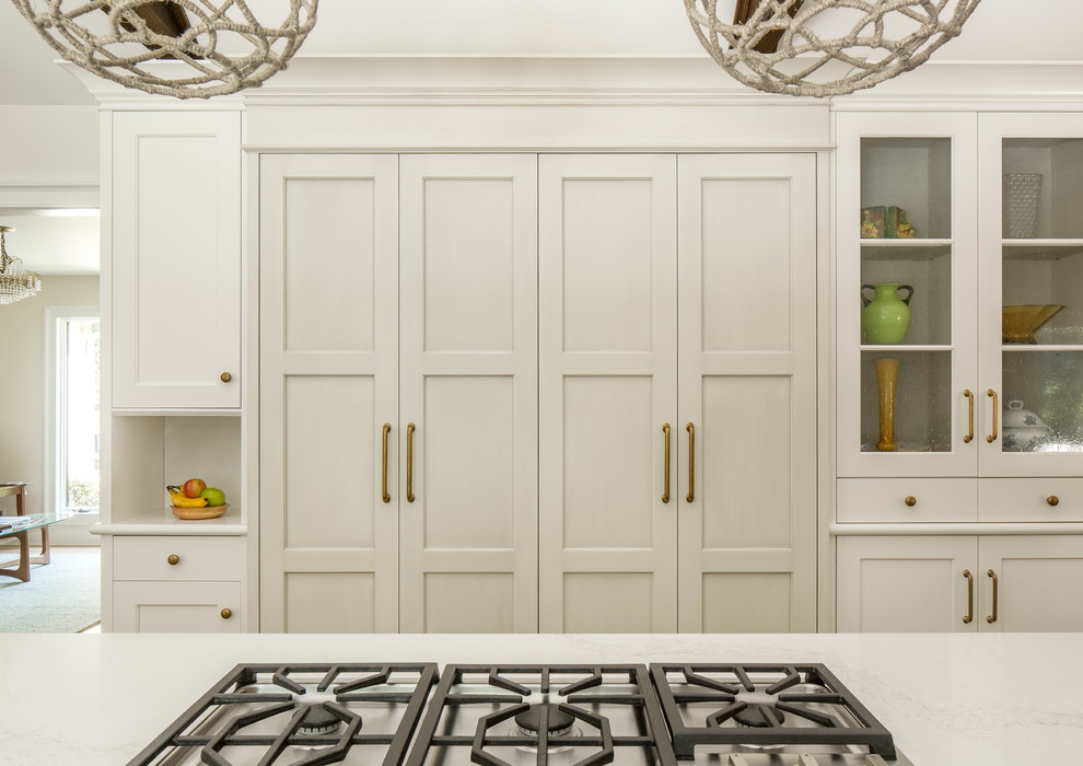 Example of a large cottage u-shaped medium tone wood floor kitchen design in New York with shaker cabinets, white cabinets, a farmhouse sink, quartz countertops, stainless steel appliances and an island