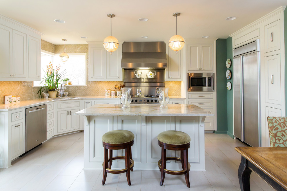 Eat-in kitchen - traditional beige floor eat-in kitchen idea in New Orleans with an undermount sink, beaded inset cabinets, white cabinets, beige backsplash, stainless steel appliances and an island