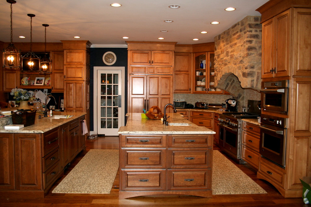 Inspiration for a mid-sized timeless u-shaped dark wood floor eat-in kitchen remodel in Raleigh with an undermount sink, raised-panel cabinets, medium tone wood cabinets, granite countertops, gray backsplash, stone tile backsplash, stainless steel appliances and two islands