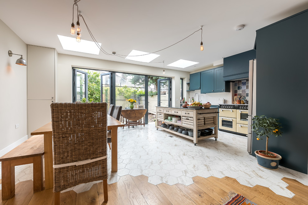 Example of a mid-sized trendy l-shaped multicolored floor eat-in kitchen design in London with a farmhouse sink, blue cabinets, blue backsplash, ceramic backsplash and an island