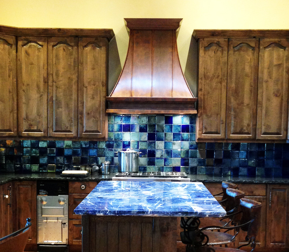 Inspiration for a mid-sized timeless l-shaped ceramic tile kitchen remodel in Austin with raised-panel cabinets, dark wood cabinets, onyx countertops, blue backsplash, porcelain backsplash, stainless steel appliances and an island