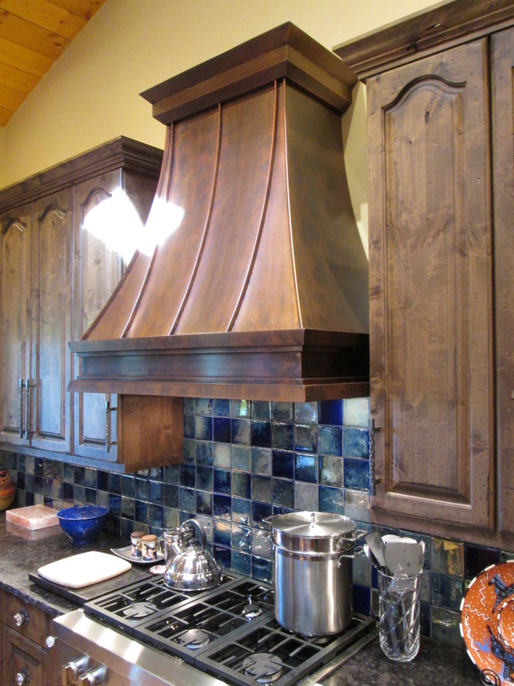 Example of a mid-sized classic l-shaped ceramic tile kitchen design in Austin with raised-panel cabinets, dark wood cabinets, onyx countertops, blue backsplash, porcelain backsplash, stainless steel appliances and an island