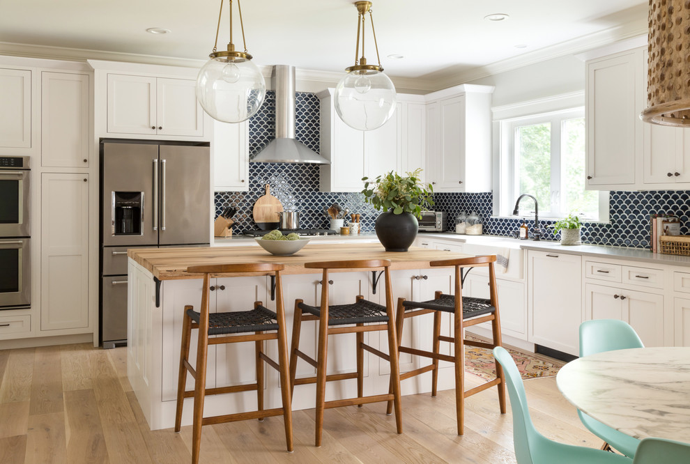 Trendy l-shaped light wood floor and beige floor eat-in kitchen photo in Boston with a farmhouse sink, white cabinets, blue backsplash, ceramic backsplash, recessed-panel cabinets, stainless steel appliances and an island