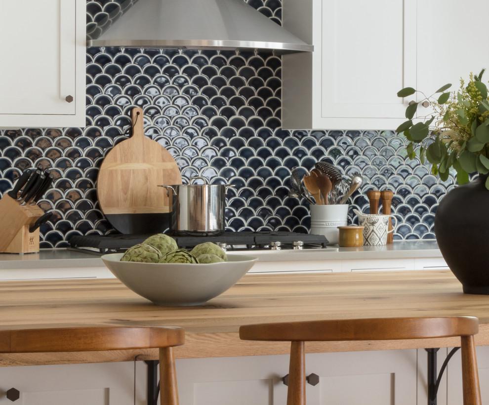Beach style light wood floor kitchen photo in Boston with a farmhouse sink, shaker cabinets, white cabinets, wood countertops, blue backsplash and ceramic backsplash
