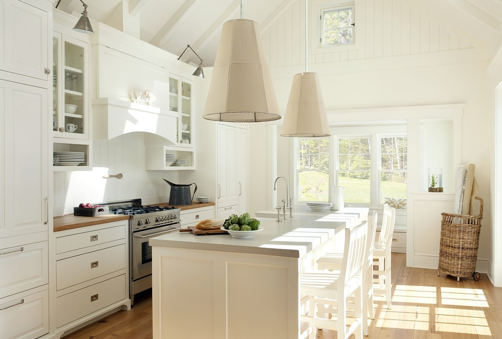 Inspiration for a beach style galley kitchen remodel in Boston with raised-panel cabinets, white cabinets, concrete countertops, white backsplash and paneled appliances