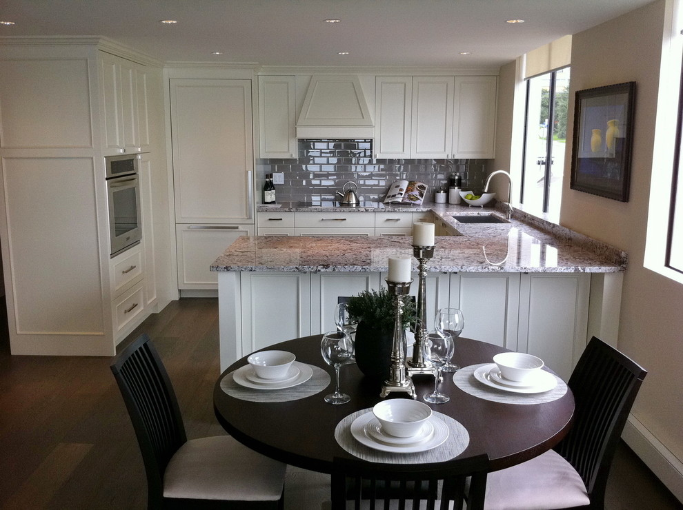 Inspiration for a mid-sized contemporary u-shaped dark wood floor eat-in kitchen remodel in Vancouver with an undermount sink, shaker cabinets, white cabinets, granite countertops, gray backsplash, stainless steel appliances, a peninsula and subway tile backsplash