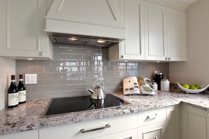 Mid-sized trendy u-shaped dark wood floor eat-in kitchen photo in Vancouver with an undermount sink, shaker cabinets, white cabinets, granite countertops, gray backsplash, subway tile backsplash, stainless steel appliances and a peninsula