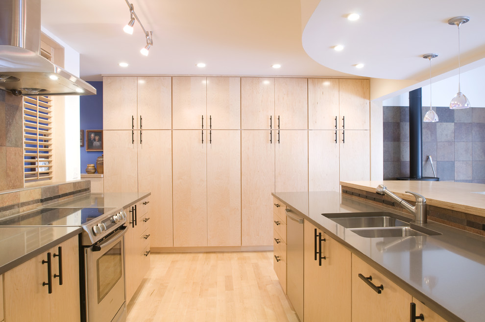 Kitchen - contemporary kitchen idea in Denver with an undermount sink, flat-panel cabinets, light wood cabinets, quartz countertops, stone tile backsplash and stainless steel appliances