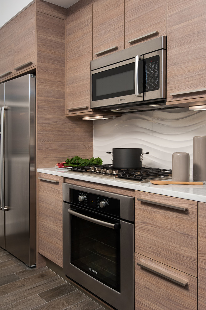 Small trendy kitchen photo in DC Metro with flat-panel cabinets, medium tone wood cabinets, beige backsplash and stainless steel appliances