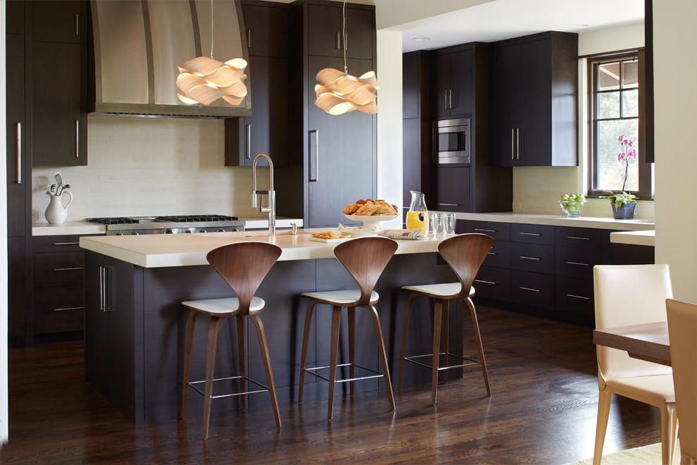 Mid-sized trendy l-shaped dark wood floor eat-in kitchen photo in San Francisco with flat-panel cabinets, dark wood cabinets, beige backsplash, an island, an undermount sink, quartz countertops, stone tile backsplash and stainless steel appliances