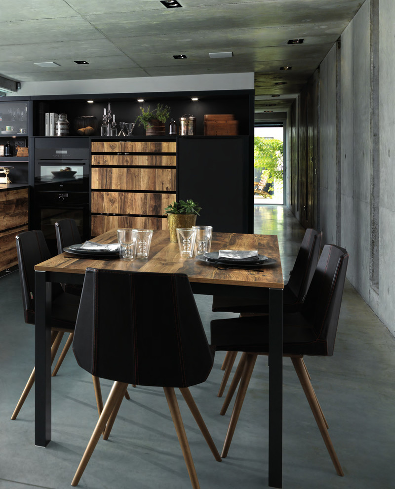 Inspiration for a mid-sized contemporary single-wall concrete floor and gray floor kitchen remodel in London with black cabinets, quartz countertops, black appliances, an island and flat-panel cabinets