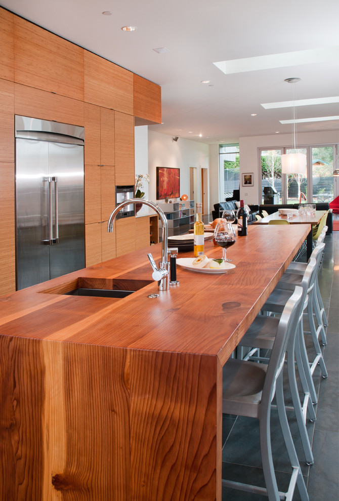 Example of a trendy galley open concept kitchen design in Vancouver with an undermount sink, flat-panel cabinets, medium tone wood cabinets, wood countertops and stainless steel appliances