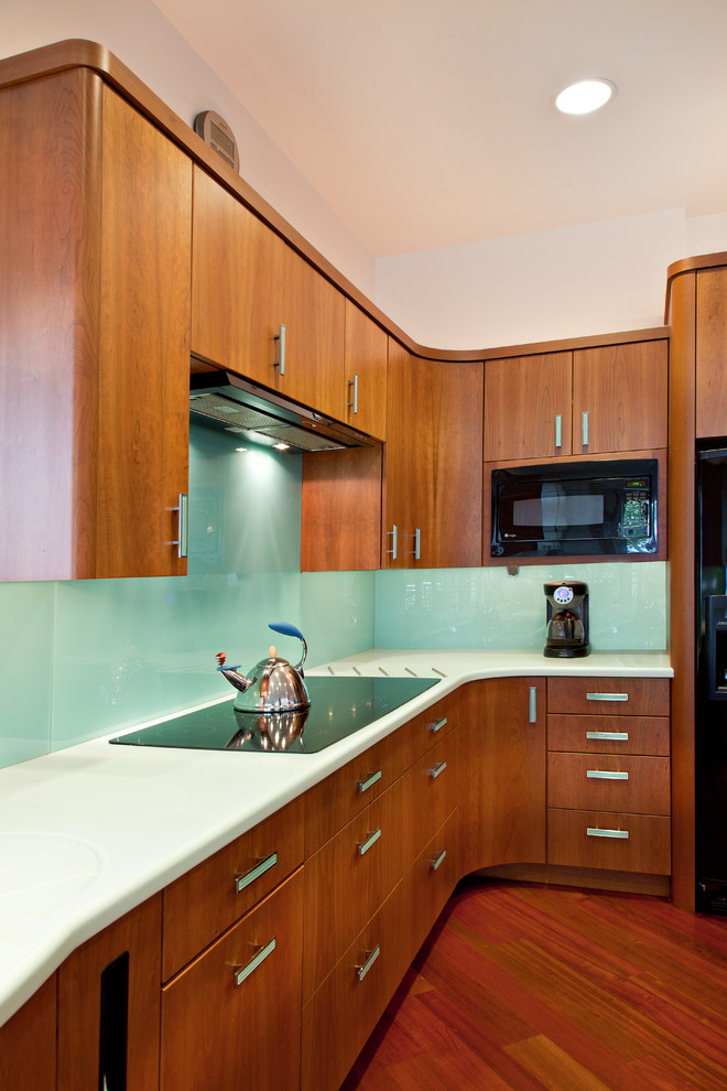 Inspiration for a contemporary kitchen remodel in Other with flat-panel cabinets, medium tone wood cabinets, glass sheet backsplash and black appliances