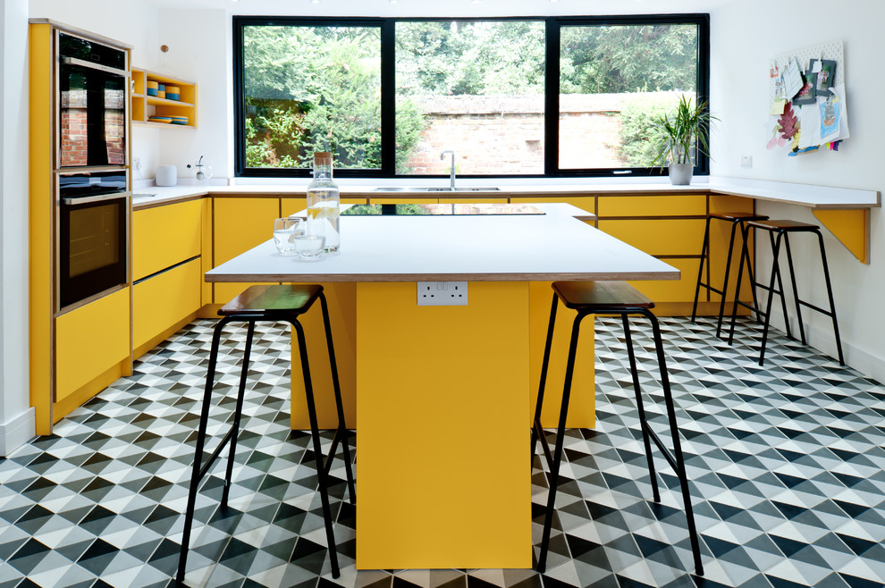 Eat-in kitchen - mid-sized contemporary l-shaped multicolored floor eat-in kitchen idea in London with flat-panel cabinets, yellow cabinets, laminate countertops, an island, white countertops, a double-bowl sink and stainless steel appliances