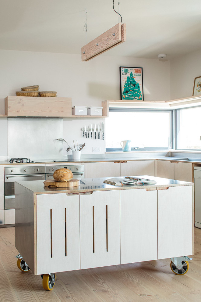 Inspiration for a mid-sized scandinavian l-shaped light wood floor kitchen remodel in Other with flat-panel cabinets, light wood cabinets, stainless steel countertops, metallic backsplash, stainless steel appliances, an island and a farmhouse sink