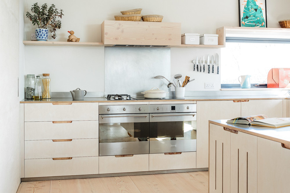 Example of a mid-sized danish l-shaped light wood floor eat-in kitchen design in Other with flat-panel cabinets, light wood cabinets, stainless steel countertops, metallic backsplash, stainless steel appliances, an island and a farmhouse sink
