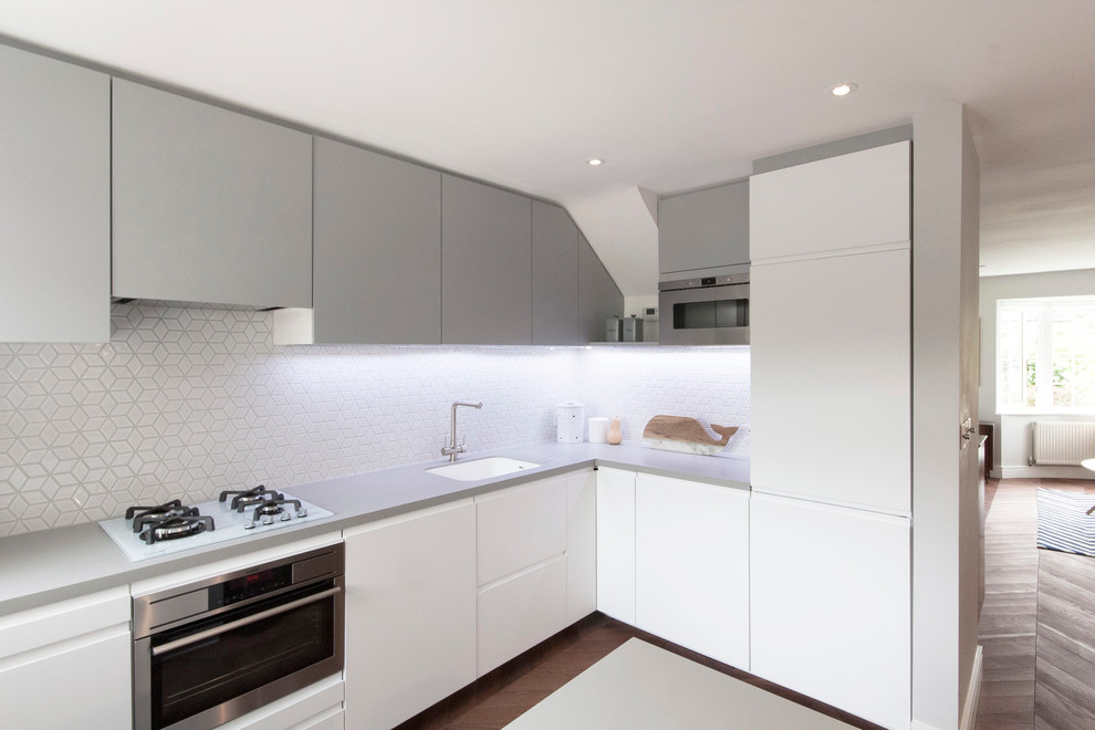 Open concept kitchen - small scandinavian l-shaped dark wood floor open concept kitchen idea in London with a drop-in sink, flat-panel cabinets, white cabinets, solid surface countertops, white backsplash, mosaic tile backsplash, stainless steel appliances and an island