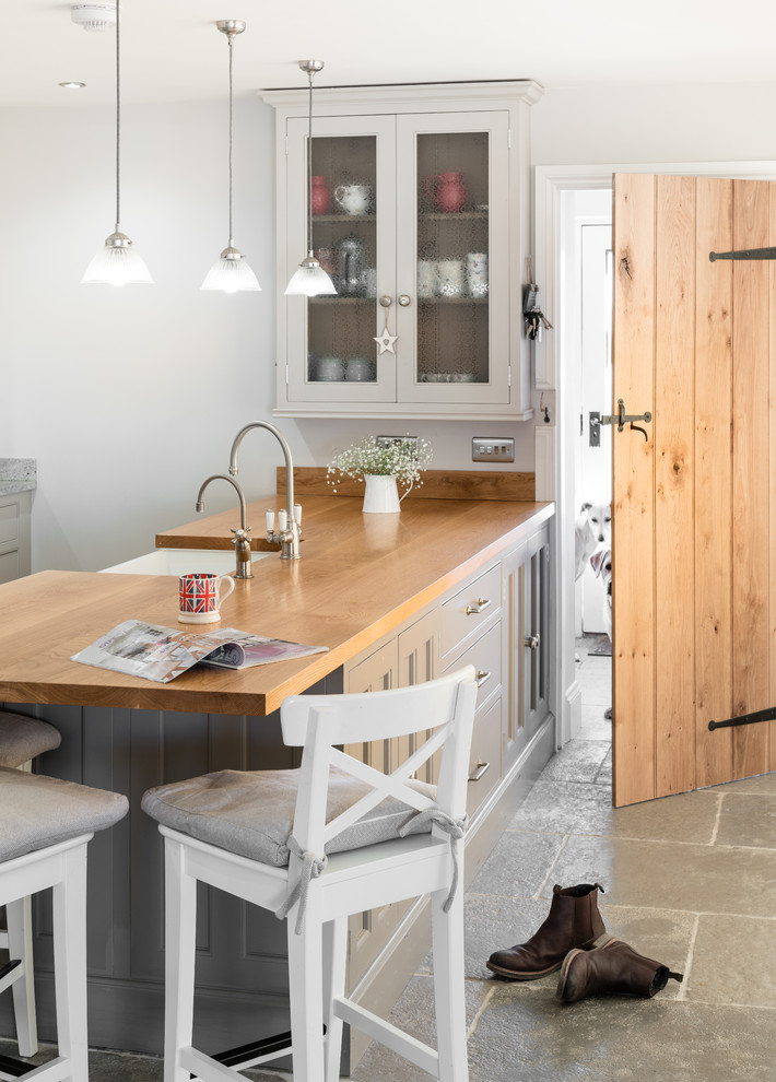 Example of a mid-sized country eat-in kitchen design in Cambridgeshire with gray cabinets and an island