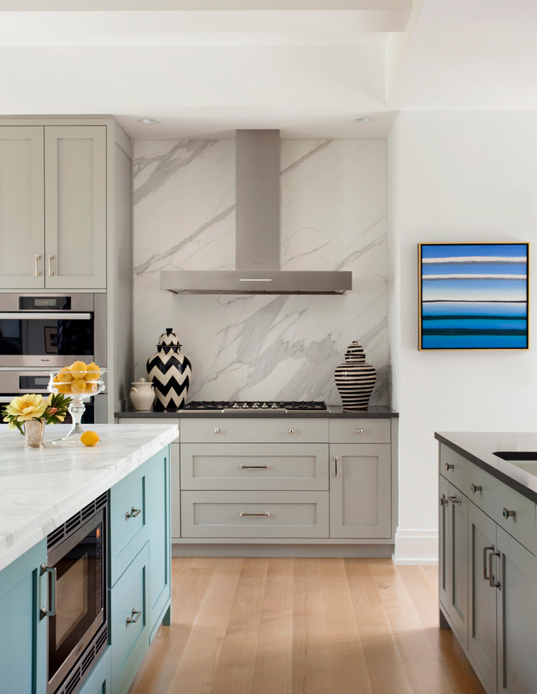 Example of a transitional light wood floor kitchen design in Boston with an undermount sink, shaker cabinets, gray cabinets, white backsplash, stainless steel appliances and marble backsplash