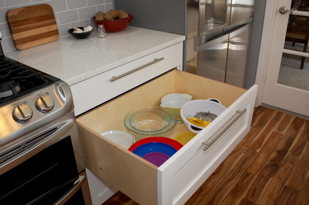 Example of a mid-sized transitional galley medium tone wood floor open concept kitchen design in Portland with an undermount sink, shaker cabinets, white cabinets, quartz countertops, gray backsplash, ceramic backsplash, stainless steel appliances, no island and gray countertops