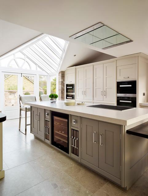 Modelo de cocina clásica renovada con armarios con paneles empotrados, puertas de armario grises y una isla