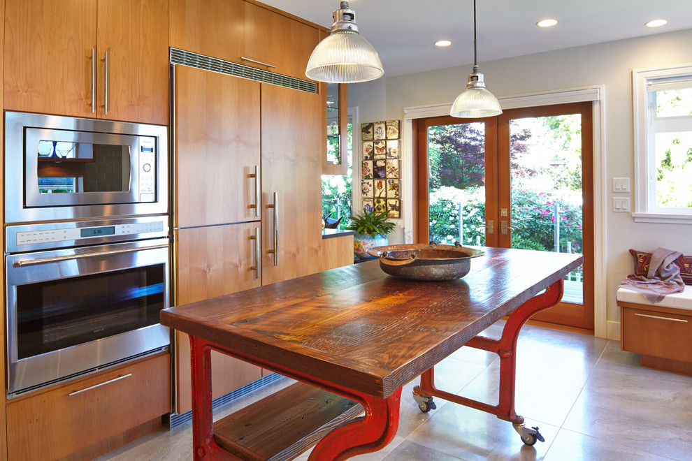 Example of a trendy u-shaped enclosed kitchen design in Vancouver with flat-panel cabinets, medium tone wood cabinets and paneled appliances